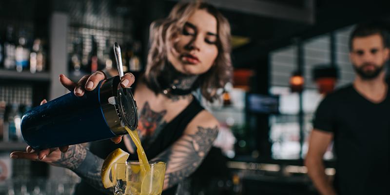 Barmaid close up of serving cocktail - landscape image