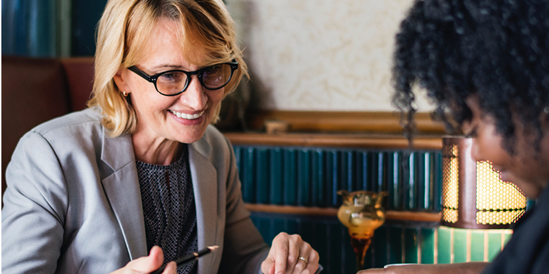Business woman speaking with colleague in cafe - landscape image
