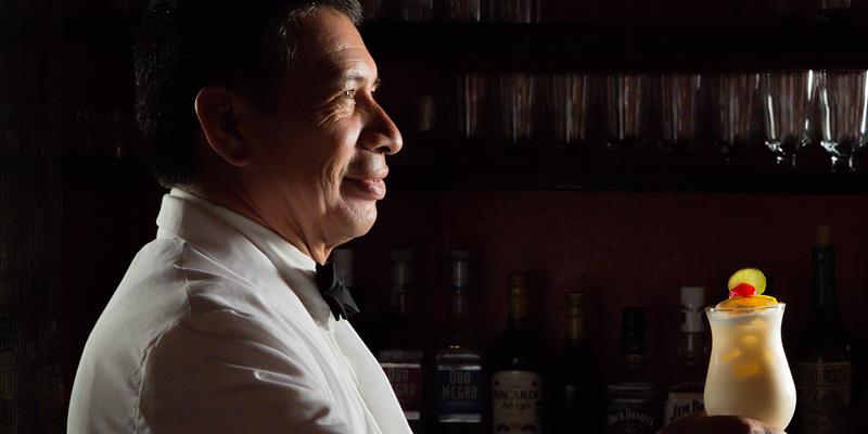 Barman serving cocktail in dark-lit bar - landscape image